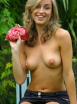 Pointy Nipples, Melanie in the garden wearing a red tie-die top with a pinstripe skirt with white cotton panties.