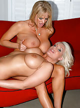 Kelly Madison and Sadie Swede sit on a cock on a red sofa.